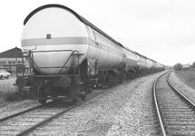 Trein met vloeistofwagons op het spoor langs de Beneluxweg. De loods...