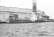 Laden van een binnenvaartschip bij de loodsen van Aug. de Meijer aan...