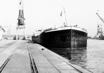Binnenvaartschip Carlo aan de kade bij bouwmaterialenhandel De Hoop in...