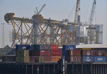 Containers op de kade bij Heerema, op de achtergrond een platform in...