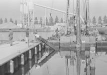 Werkzaamheden aan een kade in de Zuiderkanaalhaven. Op de achtergrond...