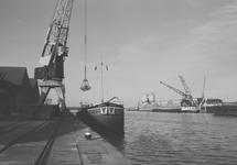 Binnenvaartschip aan het lossen bij de loodsen van Aug. de Meyer aan...