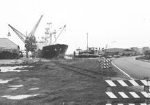 Het lossen van een schip aan de kade van de Noorderkanaalhaven. De weg...