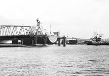 Zeeschip Dora Oldendorff vaart met behulp van sleepboten door brug...