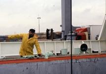 Man in oliejas aan boord van een zeeschip in de haven van...