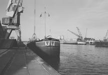 Het lossen van een binnenvaartschip bij de loodsen van Aug. de Meyer...