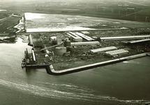 Midden op de foto de in aanbouw zijnde fabriek van Pechiney Nederland...