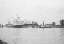 Zeeschip met sleepboot vaart door brug Sas van Gent.