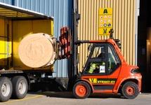 Het laden van een rol papier, met heftruck in een vrachtwagen bij...