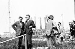 Delegatie van heren staat op de dijk bij Dow Chemical. Derde persoon...