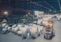 Fabriekshal met rollen staal bij Outokumpu Steel Processing op de...