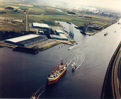 Zeeschip met sleepboten op het kanaal ter hoogte van de Zevenaarhaven.