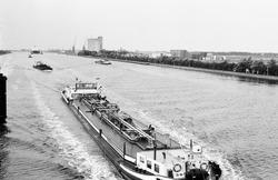 Binnenvaartschepen, en in de verte een zeeschip met sleepboten op het...