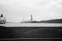 Lossen van een zeeschip met drijvende kraan bij overslagbedrijf Ovet...
