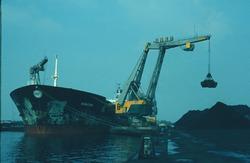 Zeeschip met drijvende kraan bij de terminal van Ovet in de...
