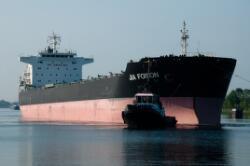 Kolenschip Jia Foison met sleepboot op het kanaal, nabij de zeesluis.