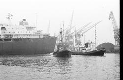 Zeeschip met sleepboten in de Zevenaarhaven.