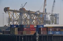 Containers op de kade bij Heerema. Op de achtergrond een platform in...