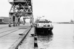 Binnenvaartschip aan de kade van de Zevenaarhaven. Op de kade de...