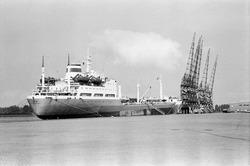 Zeeschip aan de kade van de Zevenaarhaven. Op de kade staan kranen.