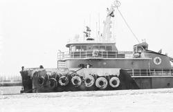 Sleepboot Gulf Cajun aan een besneeuwde kade van de Zevenaarhaven.