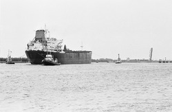 Zeeschip met sleepboten ten zuiden van de zeesluis in Terneuzen. De...