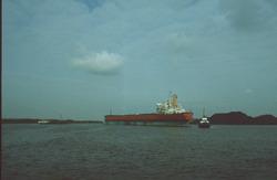Zeeschip met sleepboten in de Massagoedhaven te Terneuzen.