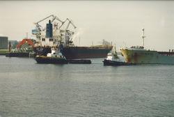 Zeeschip met sleepboten loopt de haven van Vlissingen-Oost binnen.
