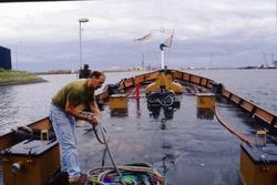 Man bij een tros aan boord van een schip in de haven van...