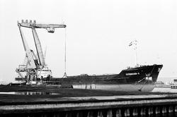 Het lossen van een zeeschip met drijvende kraan door overslagbedrijf...
