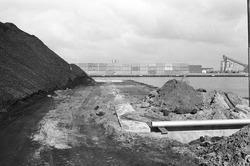 Bergen kolen op de kade van de Massagoedhaven. Op de achtergrond...