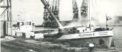 Overslag met binnenvaartschip bij de graansilo in de Zevenaarhaven.