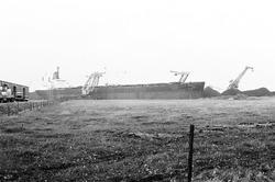 Overslag met drijvende kranen uit een zeeschip bij Ovet in de...