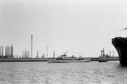 Rondvaartboot in de Braakmanhaven. Op de achtergrond de fabriek van...