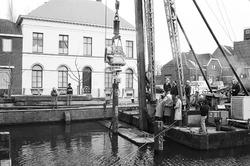 Het plaatsen van meerpalen in Zijkanaal H, Oostkade te Sas van Gent.