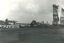Laden van een binnenvaartschip met buldozer aan de terminal van Ovet...