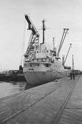 Zeeschip aan de kade met een drijvende kraan van Ovet langszij....