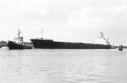 Zeeschip met sleepboten in de buitenhaven bij de zeesluis in...