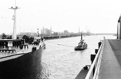 Zeeschip met sleepboot op het kanaal bij brug Sluiskil.