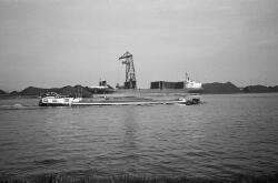 Het lossen van een zeeschip met een drijvende kraan aan de terminal...