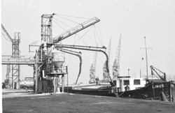 Binnenvaartschip wordt geladen aan de kade bij de graansilo aan de...
