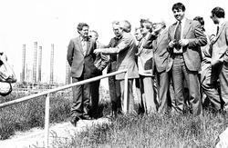 Delegatie van heren staat op de dijk bij Dow Chemical.