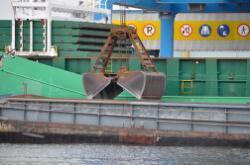 Lossen van een schip met grijper aan de bulkterminal van Verbrugge...