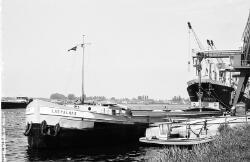 Binnenvaartschepen en een zeeschip aan de kade bij de Nederlandse...