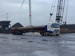 Vrachtwagen met buispalen op de kade in de Kaloothaven