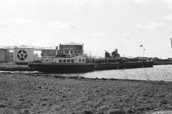 Binnenvaartschip nabij de vestiging van Texaco op het Kanaaleiland...