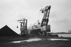 Drijvende kranen 6 en 8 van Ovet zijn een zeeschip aan het lossen in...