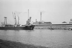Het afmeren van een zeeschip met sleepboten aan de kade van de...