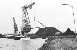 Drijvende kranen en een binnenvaartschip bij de terminal van Ovet in...