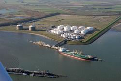Zeeschip en binnenvaartschepen aan steiger Oiltanking in de...